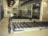Chain driven live roller conveyors with chain transfers for auto chassis assembly